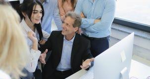 Gruppo principale dell'uomo d'affari che incontra nuova idea attuale sul computer con il gruppo di gente di affari che discute pr archivi video