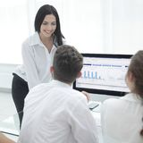 Gruppo professionale di affari che discute commercializzando i grafici al desktop immagini stock libere da diritti
