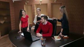 Gruppo professionale di affari che ha una riunione facendo uso del computer portatile nell'ufficio archivi video