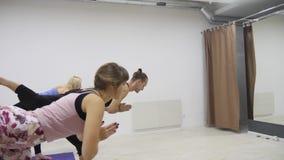 Gruppo razziale della classe di yoga multi che esercita stile di vita sano in asanas di yoga dello studio di forma fisica video d archivio