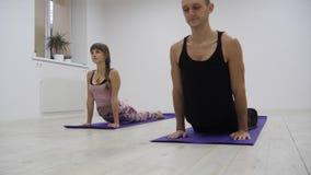 Gruppo razziale della classe di yoga multi che esercita stile di vita sano in asanas di yoga dello studio di forma fisica stock footage