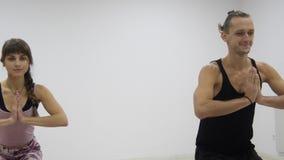 Gruppo razziale della classe di yoga multi che esercita stile di vita sano in asanas di yoga dello studio di forma fisica archivi video