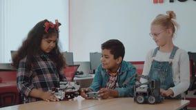 Gruppo razziale misto di bambini creativi che lavorano al progetto di tecnologia alla scuola Il ragazzo e le ragazze dello studen stock footage
