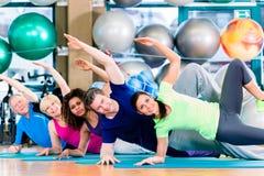 Gruppo relativo alla ginnastica in palestra che si esercita e che si prepara fotografia stock