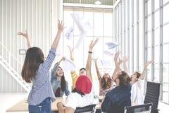 Gruppo schietto di carta di lancio e di ritenere dei documenti del giovane del gruppo prople creativo degli impiegati felice dopo fotografie stock libere da diritti