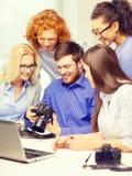 Gruppo sorridente con il computer portatile e photocamera in ufficio Immagine Stock Libera da Diritti