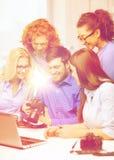 Gruppo sorridente con il computer portatile e photocamera in ufficio Fotografia Stock
