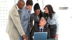 Gruppo sorridente di affari che parla intorno al computer portatile Fotografia Stock Libera da Diritti