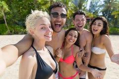 Gruppo sulle vacanze estive della spiaggia, amici sorridenti felici dei giovani che prendono l'oceano del mare della foto di Self Fotografia Stock Libera da Diritti