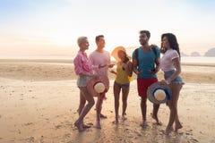 Gruppo sulle vacanze estive della spiaggia, spiaggia di camminata sorridente felice dei giovani degli amici Immagine Stock Libera da Diritti