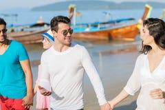 Gruppo sulle vacanze estive della spiaggia, spiaggia di camminata sorridente felice dei giovani degli amici Immagine Stock