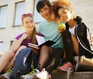 Gruppo sveglio di teenages all'università della costruzione con i huggings dei libri, nazioni di diversità Fotografia Stock