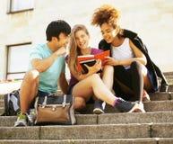 Gruppo sveglio di teenages alla costruzione dell'università con i huggings dei libri, di nuovo alla scuola Fotografia Stock