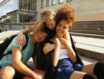 Gruppo sveglio di teenages alla costruzione dell'università con i huggings dei libri, di nuovo alla scuola Immagini Stock