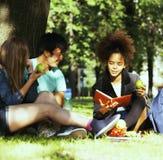 Gruppo sveglio di teenages alla costruzione dell'università con i huggings dei libri, nazioni di diversità Fotografia Stock Libera da Diritti