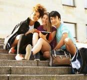Gruppo sveglio di teenages alla costruzione dell'università con i huggings dei libri, di nuovo alla scuola Fotografie Stock