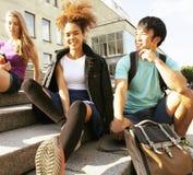 Gruppo sveglio di teenages alla costruzione dell'università con i huggings dei libri, di nuovo alla scuola Immagine Stock