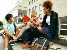 Gruppo sveglio di teenages alla costruzione dell'università con i libri Immagini Stock