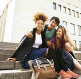 Gruppo sveglio di teenages alla costruzione dell'università con i libri Fotografia Stock