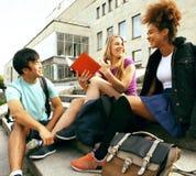 Gruppo sveglio di teenages alla costruzione dell'università con i libri Fotografie Stock