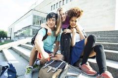 Gruppo sveglio di teenages alla costruzione dell'universit? con i huggings dei libri, stile di vita degli studenti di nazioni di  immagini stock