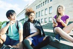 Gruppo sveglio di teenages alla costruzione dell'universit? con i huggings dei libri, stile di vita reale degli studenti di nazio fotografia stock libera da diritti