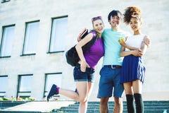 Gruppo sveglio di teenages alla costruzione dell'universit? con i huggings dei libri, stile di vita reale degli studenti di nazio immagine stock libera da diritti