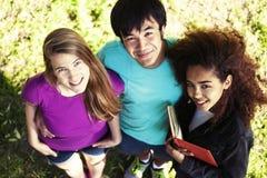 Gruppo sveglio di teenages in parco verde ad estate con i huggings dei libri, stile di vita reale degli studenti di nazioni di di immagine stock libera da diritti