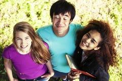 Gruppo sveglio di teenages in parco verde ad estate con i huggings dei libri, stile di vita reale degli studenti di nazioni di di fotografia stock