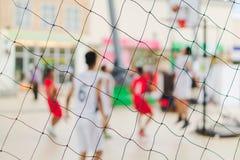 Gruppo vago astratto del fondo di gente adolescente che gioca pallacanestro della via Fuoco sul recinto netto del campo da pallac fotografia stock libera da diritti