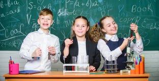 Gruppskolaelever studerar kemiska flytande Flickor och experiment f?r skola f?r pojkestudentuppf?rande med flytande Kontrollresul arkivbilder