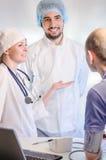 Gruppstående av medicinska doktorer och patienten arkivfoto