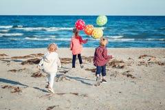 Gruppstående av roliga vita Caucasian barnungar med den färgrika gruppen av ballonger som spelar att köra på stranden på solnedgå arkivbild