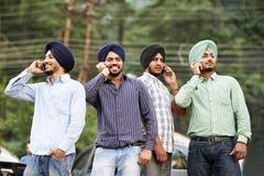 Unga indiska sikhmanar med mobil ringer Arkivfoto
