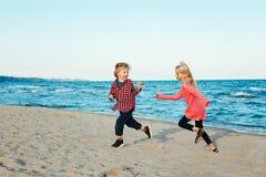 Gruppståenden av två roliga vita Caucasian barn lurar vänner som spelar att köra på stranden på solnedgång arkivbild