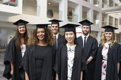 Gruppståenden av universitetet avlägger examen i lock och kappa royaltyfri foto