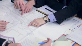 Gruppteknikerer och arkitekter diskuterar ritningen arkivfilmer