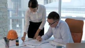 Gruppteknikerer och arkitekter diskuterar ritningen i modernt ljust kontor lager videofilmer