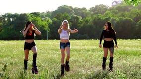 Grupputbildningskangoo Tre flickor på solnedgången i Park som gör kondition lager videofilmer