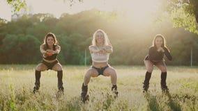 Grupputbildningskangoo Tre flickor på solnedgången utför dynamiska squats som siktas på bantningen och förstärkning av musklerna  lager videofilmer