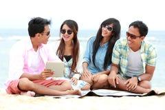 Gruppvänner som tycker om stranden, semestrar samman med minnestavlaPC Arkivbild