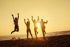 Grupy cztery przyjaciół zabawy plaży zmierzchu wakacje zdjęcie royalty free