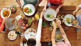 Grupy ludzi łasowanie przy stołem z jedzeniem zbiory