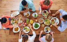 Grupy ludzi łasowanie przy stołem z jedzeniem Fotografia Royalty Free