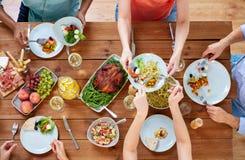 Grupy ludzi łasowanie przy stołem z jedzeniem zdjęcia stock