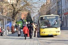 Grupy ludzi czekanie w kolejce wchodzić do lokalnego miasto autobus na autobusowym zatrzymuje stację Zdjęcia Royalty Free
