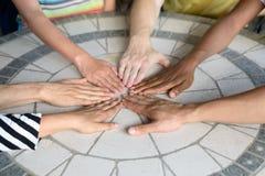 Grupy ludzi kładzenia ręki wpólnie na stole Obrazy Stock