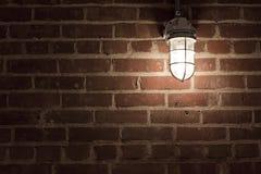 Gruselige Leuchte auf textrued Backsteinmauer Lizenzfreie Stockbilder