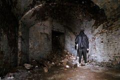 Gruseliger Mann steht im aufgegebenen Ziegelstein-Raum mit Schaufel stockbilder