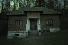 Gruseliges Geisterhaus mit dunkler Grausigkeitsatmosph?re Eine schwarze Katze und ein Vollmond hinter der schrecklichen Szene lizenzfreies stockfoto